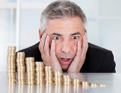 picture of descending  - Shocked Mature Businessman Looking At Descending Stack Of Coins