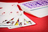 stock photo of joker  - Dealt cards on red background - JPG