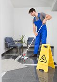 stock photo of housekeeper  - Portrait Of Young Man Cleaning The Floor With Mop In Office - JPG