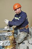 stock photo of lineman  - Electrician lineman repairman worker at huge power industrial transformer installation work - JPG