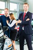 picture of showrooms  - Seller or car salesman and clients or customers in car dealership presenting the interior decoration of new and used cars in the showroom - JPG