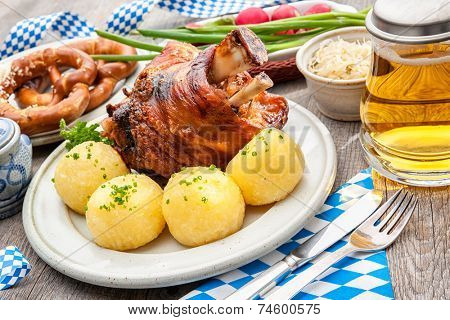 Appetizing Bavarian roast pork knuckle with dumplings and pretzel