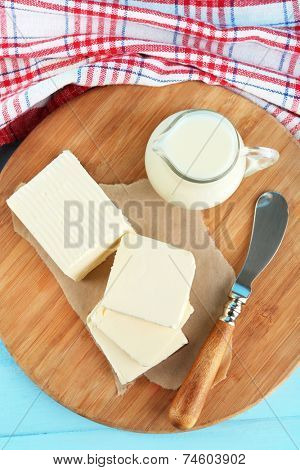 Fresh butter on cutting board and jug with milk, on color wooden background