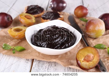 Plum jam, slices of bread with plum jam and fresh plums in glass dish on piece of paper on wooden table on light background