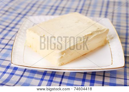 Fresh butter on plate, on table background