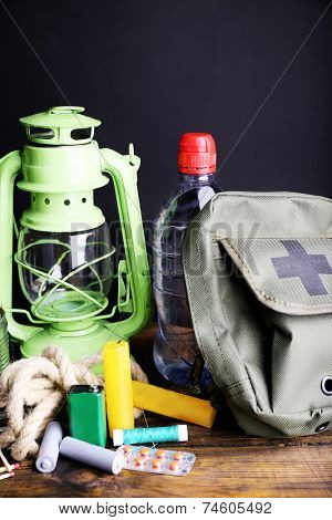 Emergency preparation equipment on wooden table, on dark background