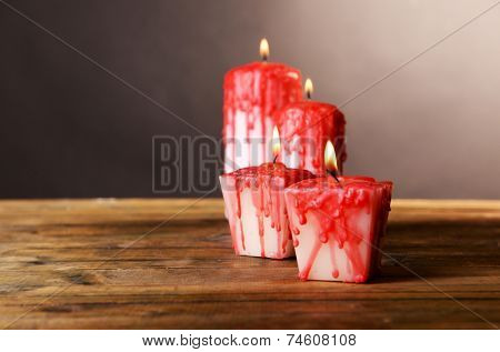 Bloody candles for Halloween holiday, on wooden table, on dark background