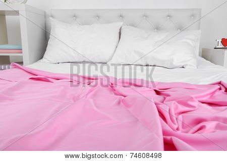 Crumpled pink linen on bed