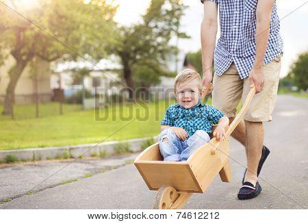Father pushing his son in wheelbarrow