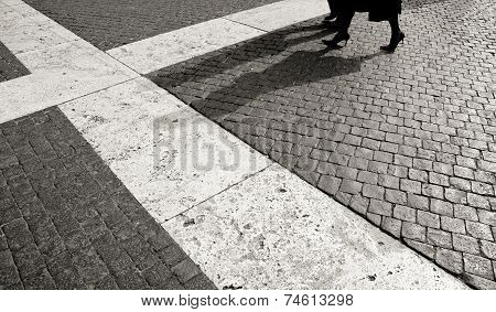 Woman And Man Walking On Cobblestone