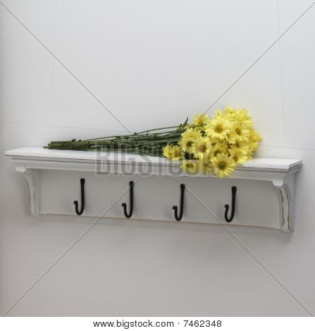 daisy flowers sitting on coat rack shelf