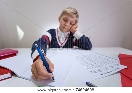 Bored Boy Writing In Notebook