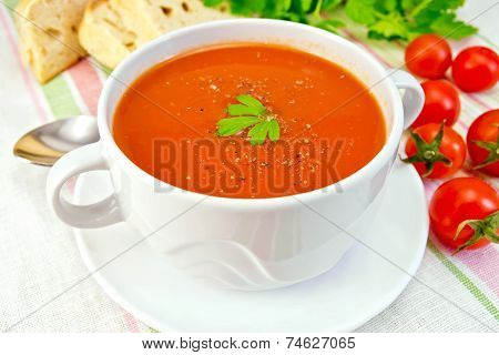 Soup tomato with peppers in bowl on linen napkin