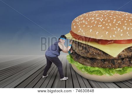 Overweight Person Pushing Big Burger