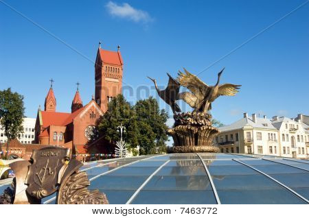 Red Church And Stork Statue