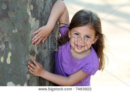 Girl touching tree trunk