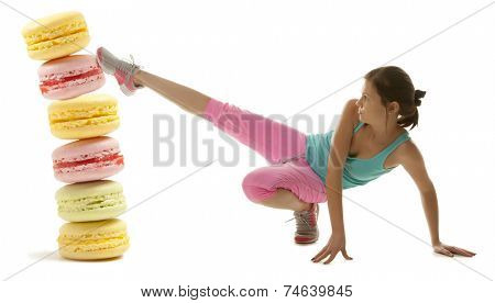 Fit young woman fighting off tasty colorful macaroon isolation on a white background