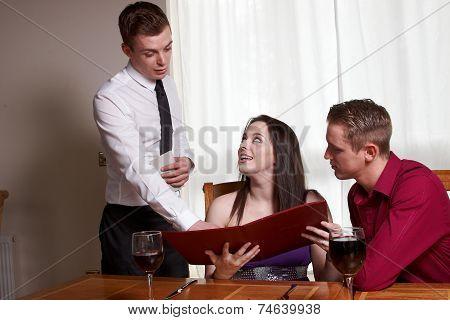 A Young Couple Reading A Menu