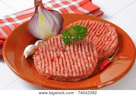 raw minced beef burger with fresh onion and garlic, on the brown plate