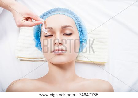 young woman remove hair from her eyebrows