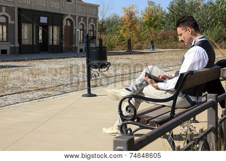Man In Old Town Relaxing Sitting On Bench Reading Book