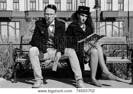 Vintage Couple Looking Serious Reading Book On The Bench