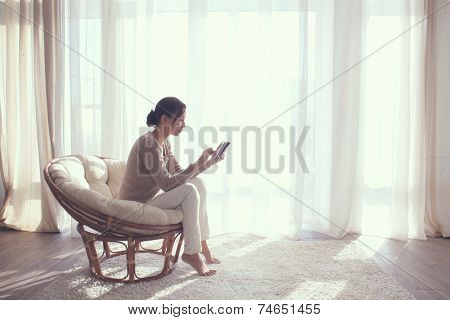 Young woman at home sitting on modern chair in front of window relaxing in her living room using tablet pc