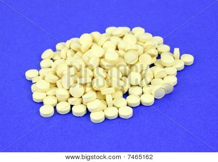 Folic acid pills on blue background