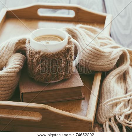 Cup of hot tea with lemon dressed in knitted warm winter scarf on brown wooden tabletop, square photo, soft focus
