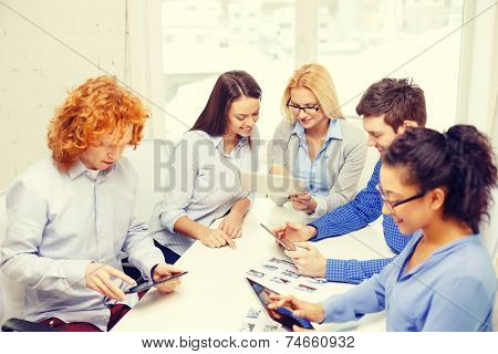 business, office and startup concep - smiling creative team with table pc computers and papers working in office