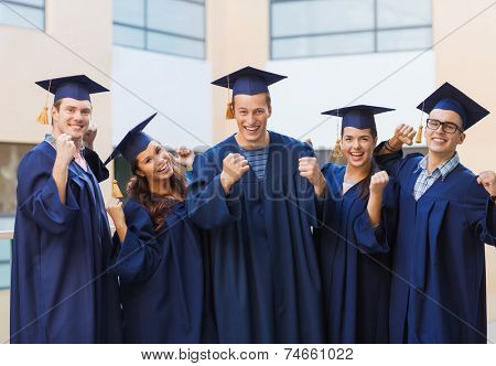 education, graduation and people concept - group of smiling students in mortarboards and gowns making triumph gesture outdoors