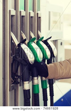 vehicle and fuel concept - close up of male hand holding fuel pump at fuel station