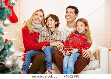 Children sitting on lap of their parents at christmas and looking at christmas tree