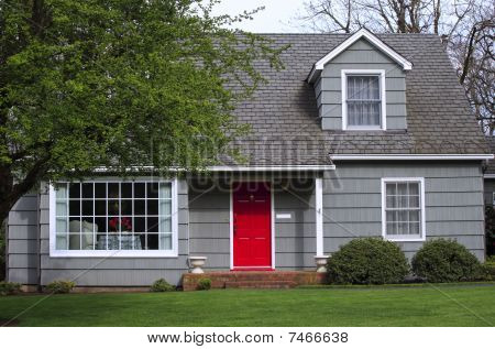 House with a red door entrance.