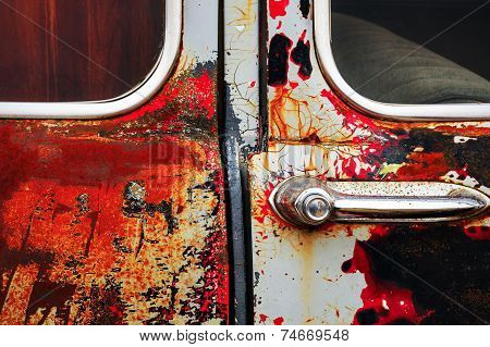 Detail image of rusty old car door with handle and lock