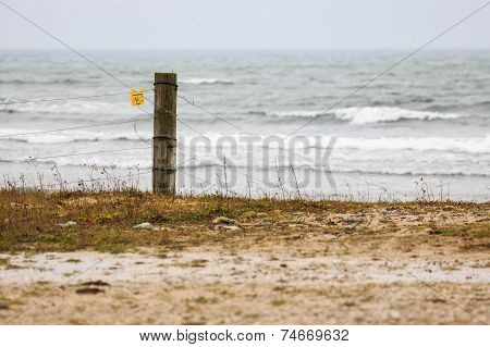 Fence post by stormy sea in Gotland, Sweden
