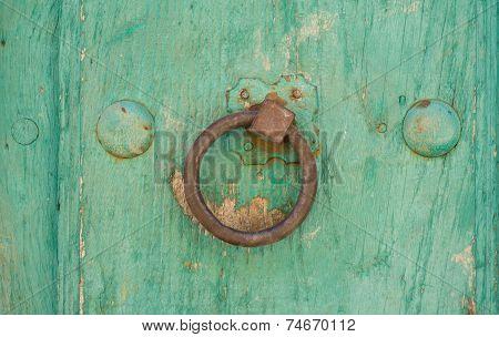 Front view of old doorknocker and green painted wooden door