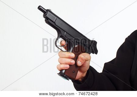Hand with discharged semi-automatic pistol on white background