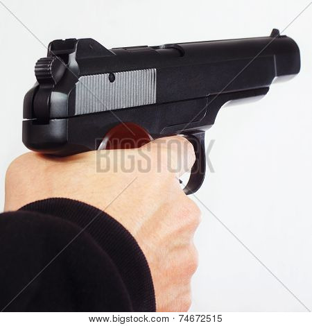 Hand with semi-automatic handgun on white background