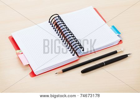 Office table with blank notepad, pen and pencil. View from above with copy space