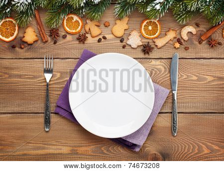 Empty plate with silverware over christmas wooden background with snow fir tree, spices, gingerbread cookies