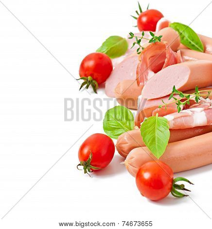 Delicate meats (sausage and ham) decorated with basil and tomatoes isolated on white background