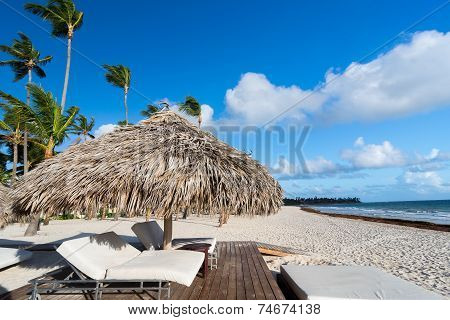 Lounger on beach with tropical sea as background under umbrella