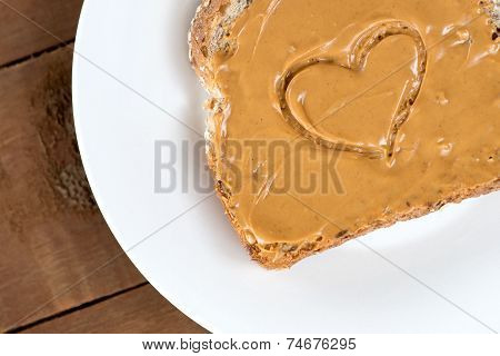 Peanut Butter Toast With Heart Shape On White Against Wooden Board