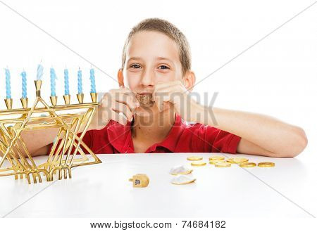 Little boy playing driedel and eating gelt on Hanukkah.  White background.