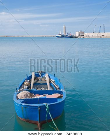 Landscape of Molfetta Seaport with close up of rowboat. Apulia.