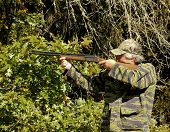 foto of shotgun  - Mature man hunting with a shotgun with a woods and forest background - JPG
