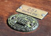 stock photo of coin slot  - coin slot with markings on an old wooden antique background  - JPG