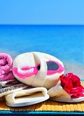 image of pumice-stone  - Natural bath sponges bath slippers pumice and towel against blue ocean - JPG