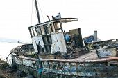 stock photo of derelict  - Derelict fishing trawler hauled up and rotting in a sea estuary - JPG